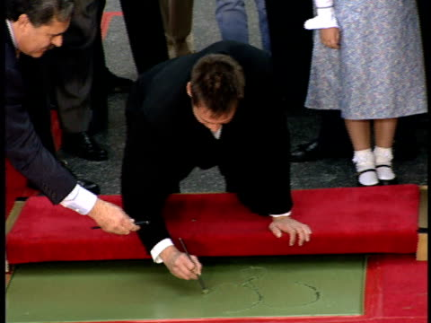 Carrey writes in wet cement at his induction into the Hollywood Walk of Fame