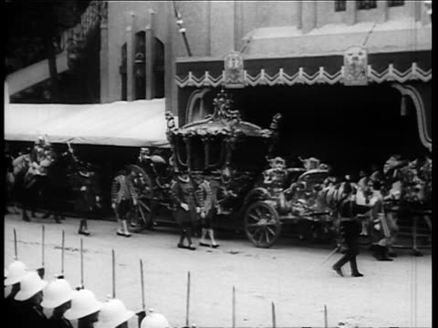 carriage carrying george vi to coronation on london street / cavalry in royal procession / men saluting before royal carriage / crowd gathered to... - coronation stock videos and b-roll footage