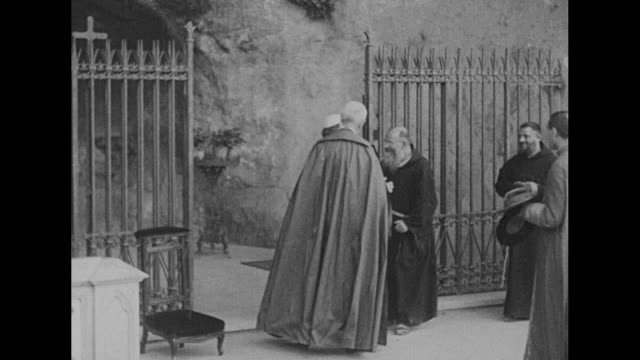 carriage pulled by two horses passes / at barred grotto pius xi attended by two priests in long capes stands while monks and african priests kiss his... - priest stock videos and b-roll footage