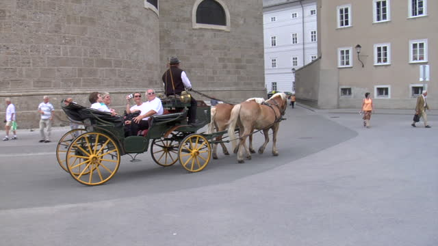 vidéos et rushes de carriage wagon with sight-seeing tourists is pulled by haflinger or belgian horses is pulled through the streets of salzburg - voiture hippomobile