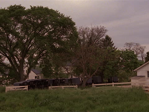 carriages sit in a row on an amish farm. - amische stock-videos und b-roll-filmmaterial
