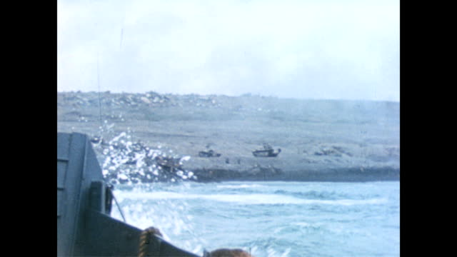 Carrier comes to shore / soldiers crouched fully armed on beach / looking at coastline see military vehicles dotted along the shore line / from the...