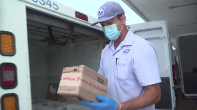 "carrier oscar osorio says that wearing a face mask and gloves during his daily delivery route is ""now part of the routine that keeps us safe and... - mail stock videos & royalty-free footage"