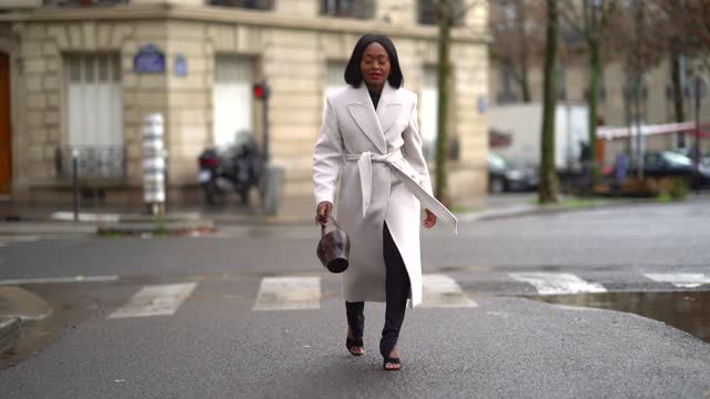 carrole sagba aka lianose wears a gray/white wool long double breasted trench coat from & other stories, a brown leather crocodile pattern bag, black... - hairstyle stock videos & royalty-free footage