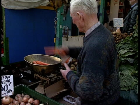 vidéos et rushes de carrot pesticide scare islington chapel market ms bobby redrupp selecting carrots from his stall and showing them to old woman customer cms redrupp... - chapelle