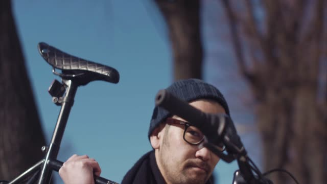 vídeos de stock e filmes b-roll de carrying a bike to the cafe (slow motion) - east asian ethnicity