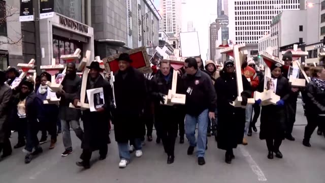 carrying a cross for every life lost to gun violence this year hundreds take to chicago streets on new year's eve to protest the 57 percent uptick in... - gun crime stock videos & royalty-free footage