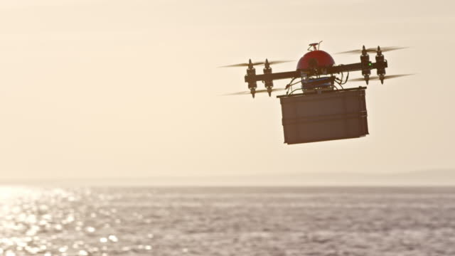 slo mo uav carrying a package across sea at sunset - delivering stock videos & royalty-free footage