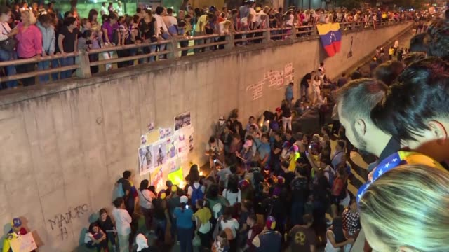 Carrying candles thousands of opposition supporters march Thursday night in eastern Caracas to the site where a 17 year old boy died the day before...