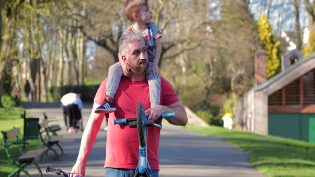 carrying his son on his shoulders in the park - carrying on shoulders stock videos & royalty-free footage