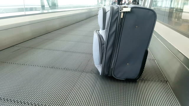 carry-on luggage rides moving walkway in airport - carry on luggage stock videos and b-roll footage