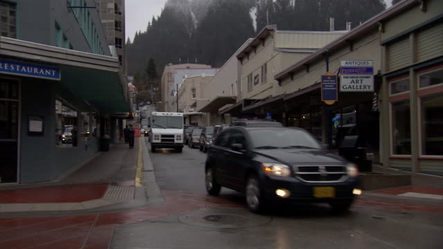 cars and a mail truck drive a rain-dampened street in juneau, alaska. - juneau stock videos and b-roll footage