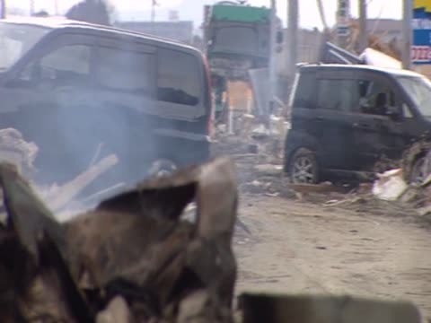 cars and a wheel lies amongst the rubble of a town destroyed by the tsunami japan march 2011 - 荒廃した点の映像素材/bロール