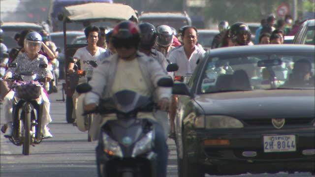 Cars and bikes running around in the city: Medium Shot.