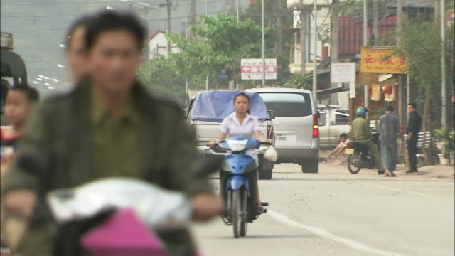 Cars and bikes running in the town of Louang Namtha: Pan up.