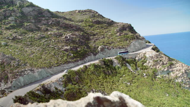 cars and bus going up a mountain road by the sea, dolly wide shot - カランシェ点の映像素材/bロール