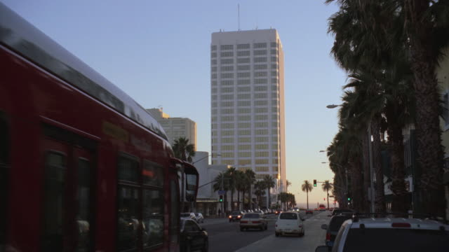 ws cars and buses driving by on busy street lined with palm trees and skyscraper beyond / beverly hills, california, united states - beverly hills california stock videos and b-roll footage