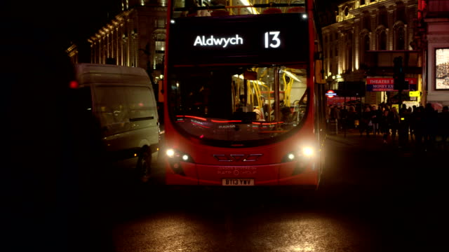 Cars and buses pass by at Piccadilly Circus in London in slow motion at night.