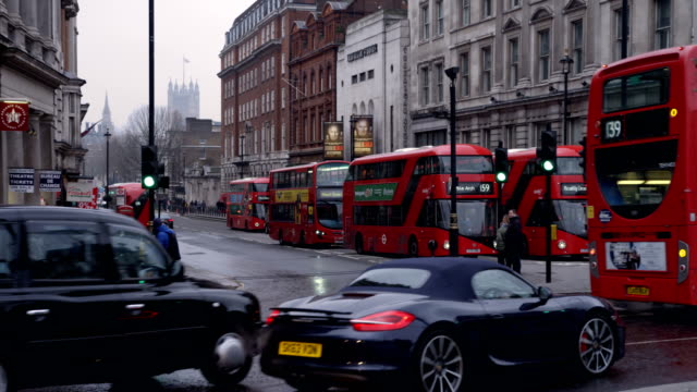 vídeos de stock e filmes b-roll de cars and buses pass by in slow motion at whitehall in london in slow motion with slight rain - reino unido