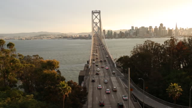 stockvideo's en b-roll-footage met cars and busses traveling over the bay bridge with the sun setting behind it. - hangbrug