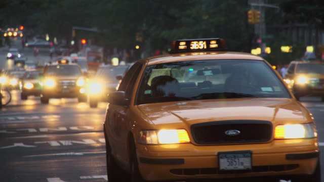 Cars and cabs turn in front of the camera at dusk in New York City.  Central Park West
