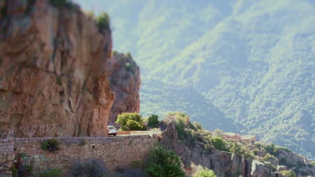 cars and cyclist take slow turn on windy mountain road, t/s - カランシェ点の映像素材/bロール