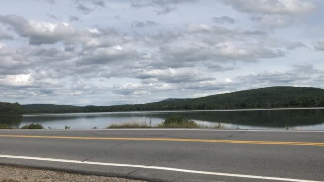 cars and motorcycles driving down route 16 in dummer, new hampshire usa - 国有林点の映像素材/bロール