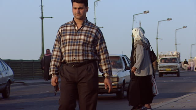 vídeos de stock, filmes e b-roll de cars and pedestrian traffic, two veiled women crossing the street on a bridge over the tigris. al mustansiriya minaret in the background. an example... - madressa
