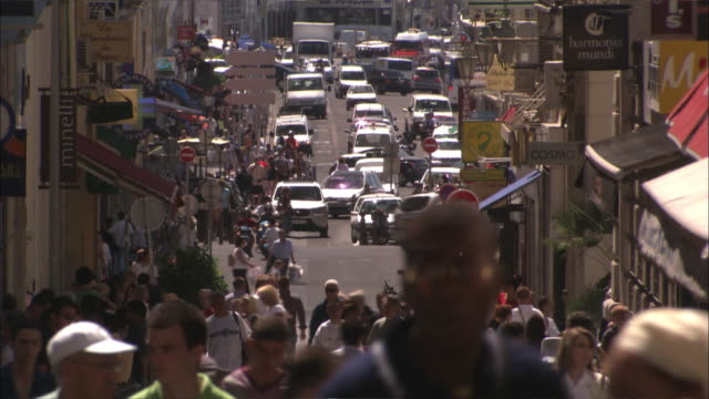 vidéos et rushes de cars and pedestrians crowd a busy street in a marseilles retail district. - marseille