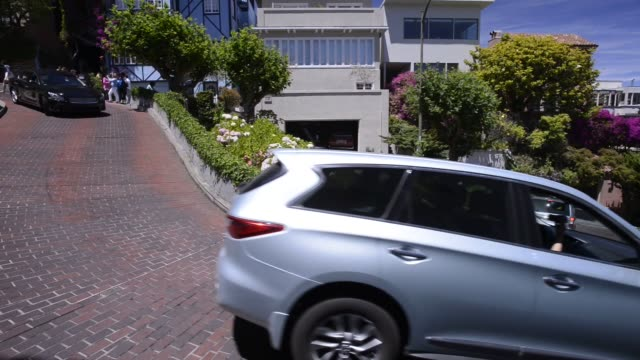vídeos de stock, filmes e b-roll de cars and pedestrians drive and walk down lombard street in san francisco california us shots pan around one of lombard streets curves as a cars drive... - lombard street san francisco