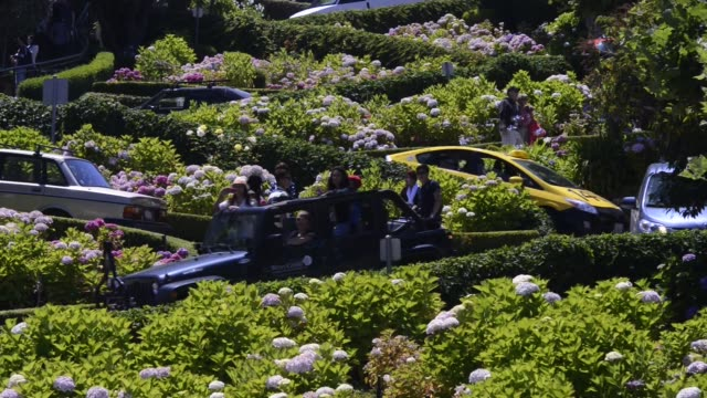 cars and pedestrians drive and walk down lombard street in san francisco california us shots of cars turning off of lombard street at the bottom of... - lombard street san francisco bildbanksvideor och videomaterial från bakom kulisserna