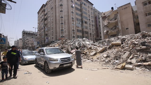 cars and pedestrians passing rubble of building left after israeli airstrikes in gaza city. factories, residential buildings, commercial buildings... - rubble stock videos & royalty-free footage