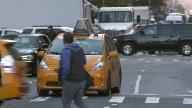 Cars and people cross in front of taxi waiting at stoplight on busy New York City street.