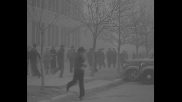 cars and school bus move through street in haze of dust / pedestrians cross street and walk down sidewalks / two young women wearing coats and hats... - dust bowl stock videos and b-roll footage