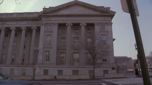 la cars and taxis passing on street on side of u.s. treasury building / washington, d.c., united states - 財務省ビル点の映像素材/bロール