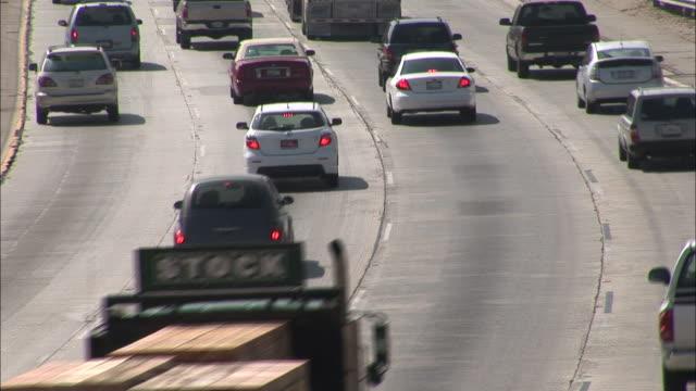 cars and trucks drive down a four lane la freeway. - 主要道路点の映像素材/bロール