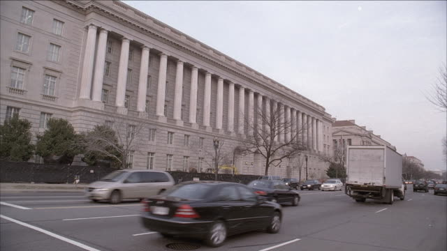 vídeos de stock e filmes b-roll de ms cars and trucks driving on a busy, large, multi-lane road in front of an old building with pillars / washington, d.c., united states - grupo médio de objetos