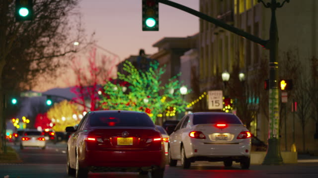 cars and trucks driving on street with green traffic light at night / provo, utah, united states - provo stock-videos und b-roll-filmmaterial