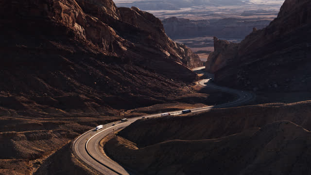 cars and trucks on freeway in san rafael swell with dramatic lens flare - winding road stock videos & royalty-free footage