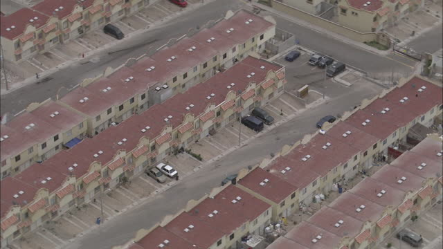 cars and trucks park on the streets around a massive housing development. - housing development stock videos & royalty-free footage