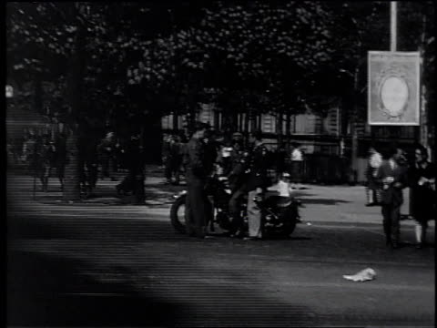 stockvideo's en b-roll-footage met cars and trucks pass in front of soliders talking to m.p. / m.p. drives toward camera as soldiers follow, walking across the street / paris, france - mp