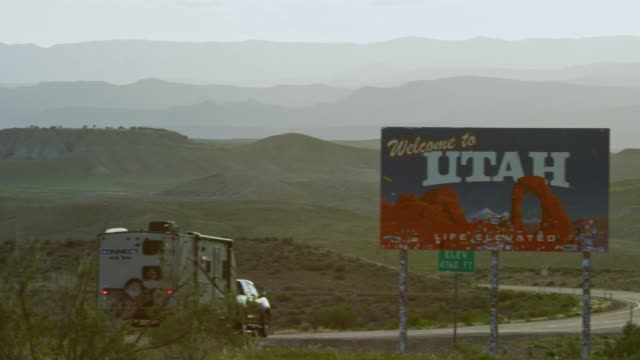 """Cars and Vehicles Drive by as the Camera Pans from Interstate 70 to the """"Welcome to Utah"""" Sign on the Utah/Colorado Border (Eastern Utah) with Mountains in the Background"""