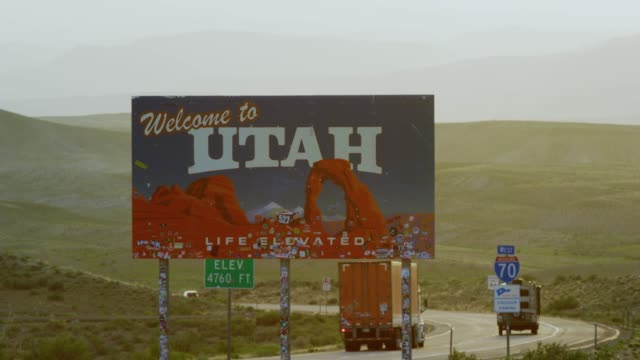 "cars and vehicles drive by as the camera pans from interstate 70 to the ""welcome to utah"" sign on the utah/colorado border (eastern utah) with mountains in the background - general view stock videos & royalty-free footage"