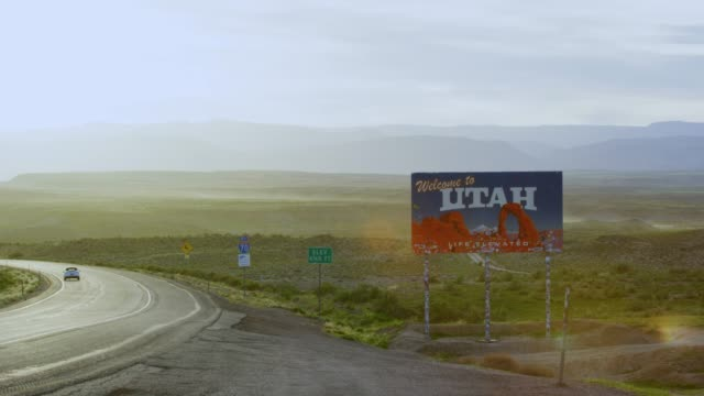 "vídeos de stock e filmes b-roll de cars and vehicles drive by as the camera pans from interstate 70 to the ""welcome to utah"" sign on the utah/colorado border (eastern utah) with mountains in the background - sinal de estrada"