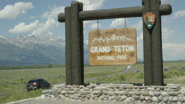 "cars and vehicles drive by the ""grand teton national park"" sign by the side of the road with the grand teton mountains in the background on a sunny day in western wyoming - grand teton stock videos & royalty-free footage"