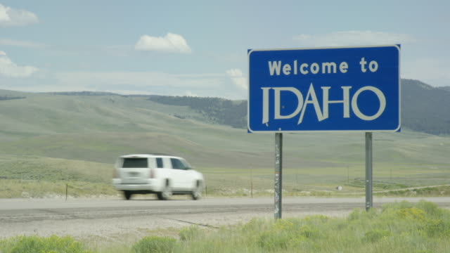 """cars and vehicles drive by the """"welcome to idaho"""" state sign on the wyoming/idaho border with mountains in the background on a sunny day - welcome sign stock videos & royalty-free footage"""