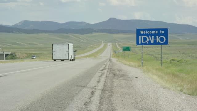 """vídeos y material grabado en eventos de stock de coches y vehículos pasan por el letrero estatal """"bienvenido a idaho"""" en la frontera de wyoming/idaho con montañas en el fondo en un día soleado - cartel de bienvenida"""