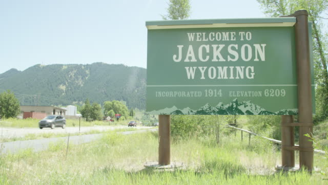 """cars and vehicles drive by the """"welcome to jackson, wyoming"""" sign by the side of the road with mountains in the background on a sunny day - jackson stock videos & royalty-free footage"""