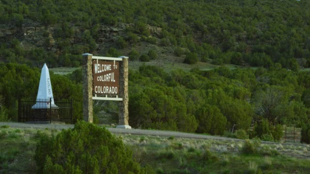"""Cars and Vehicles on Interstate 70 Drive East by the """"Welcome to Colorful Colorado"""" Sign and an Obelisk as They Enter Colorado from Utah"""