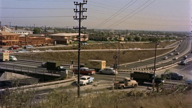 stockvideo's en b-roll-footage met 1955 montage ha ws cars at highway over-pass intersection / los angeles, united states - 1955